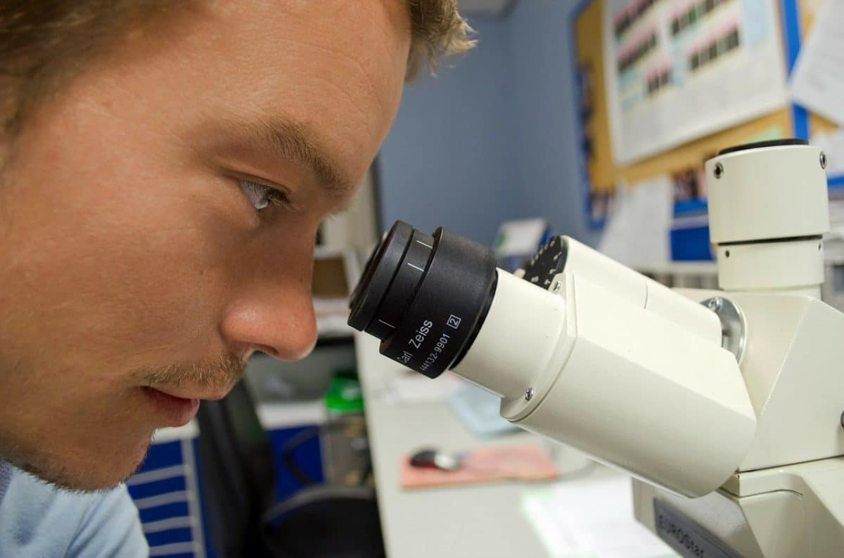 Man looking through microscope.